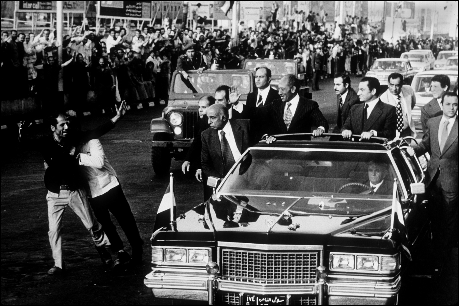 Egyptian President Anwar Sadat waves from his limousine as motorcade drives into Cairo from the airport. Sadat was returning from Washington, DC. : Sadat-Mubarak 1978-1981 : BILL FOLEY