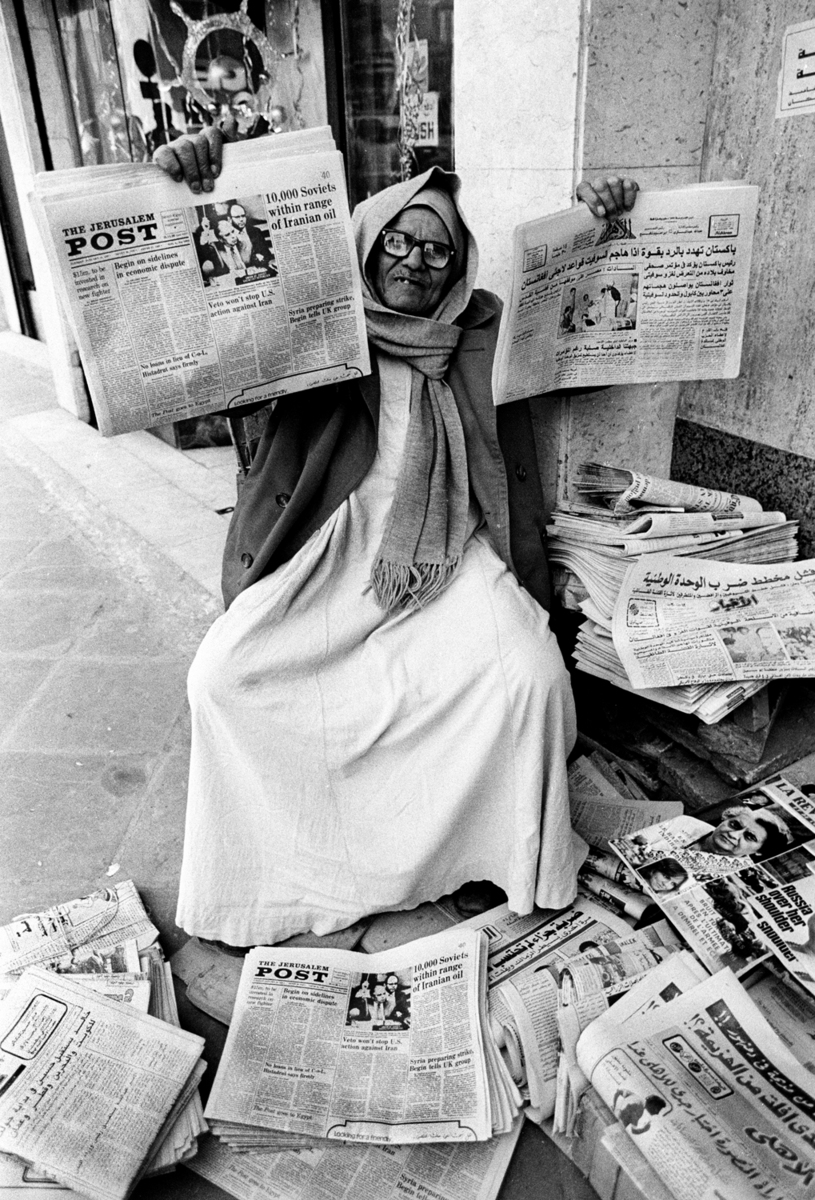 Mustapha, a newspaper vendor holds up the Jerusalem Post with the Egyptian Al-Ahram newspaper. Israeli newspapers were sold in Cairo after the Camp David agreement between Egypt and Israel was signed. : Sadat-Mubarak 1978-1981 : BILL FOLEY