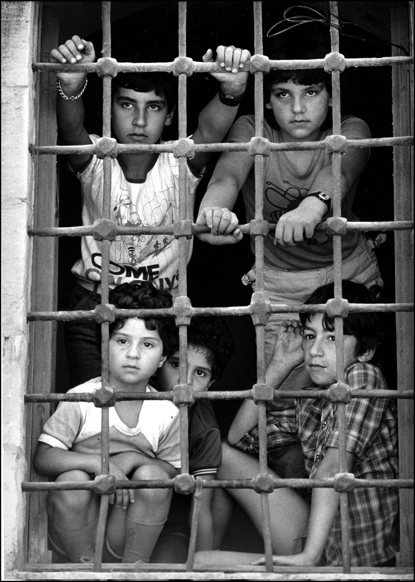 Refuge, Christian kids look out window of a church in Deir el Khamar, watching supplies being delivered during Chouf War. : Lebanon 1981-2008 : BILL FOLEY