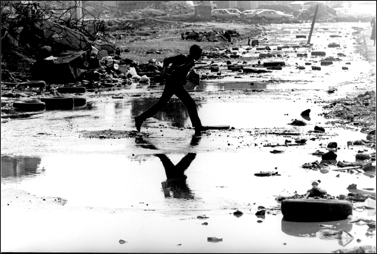Sabra Palestinian camp. Young boy jumps over puddle in the camp's main street. 1982 : Lebanon 1981-2008 : BILL FOLEY