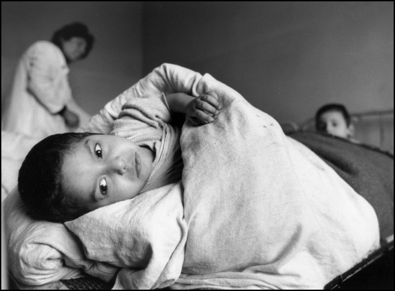 Child looks from his bed as nurse and other kid looks on. 1992 : Albania 1992 : BILL FOLEY